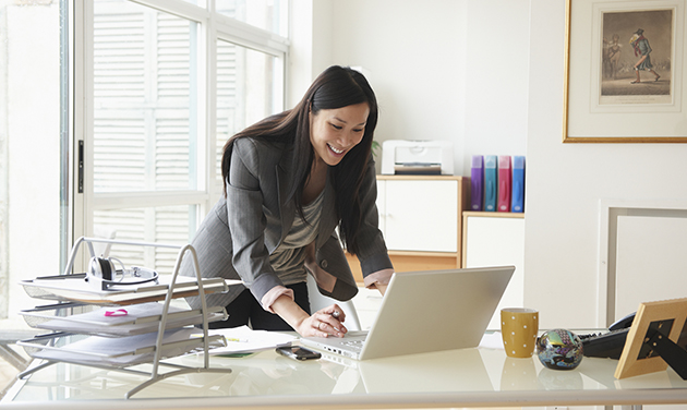 Woman hovering over computer working at desk