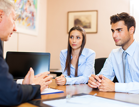 Photo of an advisor talking to a man and woman.