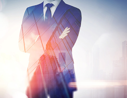 Photo of a man in a suit crossing his arms with a cross fade of a building.