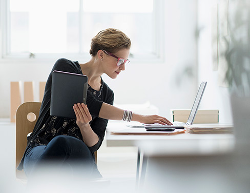 business woman working on laptop and device