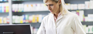 Female pharmacist looking at desktop screen