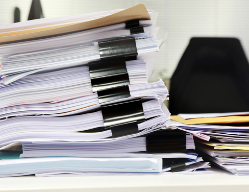 A huge stack of paper documents on a desk.