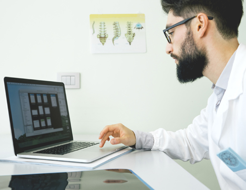 Doctor using laptop computer.