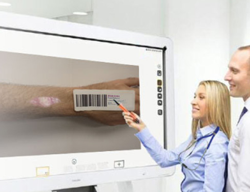 Ricoh Interactive Whiteboard with two doctors reviewing wound of patient