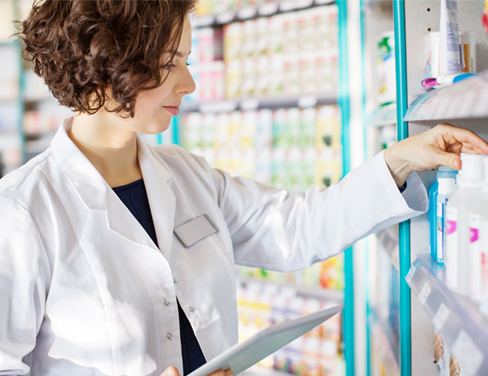 Young pharmacist with a digital tablet in drug store checking medicines on the shelf.