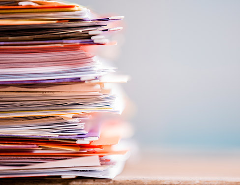 Photo of a closeup stack of papers and files on a desk.